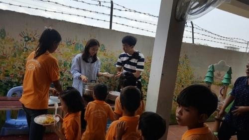 신혼여행 대신 봉사 해외 봉사활동을 떠난 송제안(가운데)-김도형(오른쪽) 씨 부부가 캄보디아의 한 어린이 교육시설에서 급식 봉사활동을 하는 모습. [송제안씨 제공=연합뉴스]